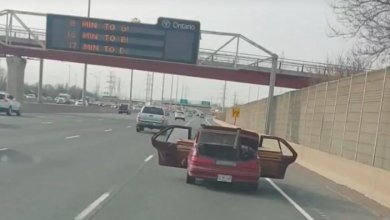Photo of QEW driver caught on video with car doors open, carting load of wood