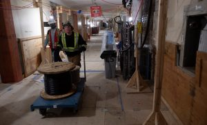Workers transport a roll of wire through the basement hallway of Centre Block-Milenio Stadium-Canada