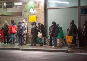 Homeless people line up outside a Montreal hotel-Milenio Stadium-Canada