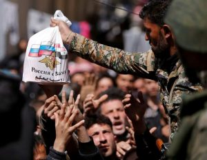 A Syrian army soldier distributes aid from Russian forces to civilians-Milenio Stadium-Canada