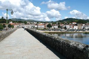 There are more than enough reasons to visit the oldest Portuguese town. Choose from its museums or rich history and don't forget the local cuisine and the lagoons just outside Ponte de Lima. Besides, this town is also one of the best stops for a rest day if you're walking the Portuguese Central Camino de Santiago. The most iconic image of lovely Ponte de Lima is, without a doubt, that of the bridge over the river Lima with the 18th century church of Santo António da Torre Velha and the Guardian Angel Chapel on the side opposite to the town centre. The bridge, both Roman and medieval, crosses the river Lima, the main character in a legend dating back to Roman times and which tells the story of a group of soldiers who were too scared to cross the river. They believed the Lima was in fact the Lethe, the river of forgetfulness in Greek mythology, and crossing it meant forgetting everything, including their family and their homeland. The consul decided to cross the river alone to convince them they were wrong and, having reached the other margin, called the soldiers one by one, proving them the Lima was not the Lethe. The mock Roman troops made of wood that you'll find near the bridge act as a reminder of this legend. Interested in exploring the art of azulejo, Portuguese painted tiles? In Ponte de Lima you'll find several tile panels, both traditional and modern, illustrating scenes of legend and history, landscapes and even poems. You can take the Rota dos Azulejos (Tile Route) pedestrian route to make sure you don't miss a single one. After a stroll along the river bank, make a little time for a drink and a snack in Largo do Camões, the central plaza that provides the perfect backdrop to relax and watch life go by. While in the historical part of Ponte de Lima don't forget to visit the Gothic church (Igreja Matriz), the 14th century prison tower (Torre da Cadeia Velha) and the 17th century fountain. The Center for the Interpretation of the Territory (Centro de Interpretação do Território) is also worth visiting to become acquainted with objects that used to be part of the daily lives of the people in the region: from bread and wine making to folklore, weaving and the production of linen, among other areas. Also worthy of your time while in Ponte de Lima are the Museum of the Third Order (Museu dos Terceiros) and the Portuguese Toy Museum (Museu do Brinquedo Português): the first is the most important reference in terms of religious art in the north of Portugal, occupying both the former Convent of Santo António dos Capuchos and the building of the Third Order of Saint Francis; the latter takes you on an amazing journey through the world of toys made in Portugal, from the late 19th century until 1986. Maybe you'll see some toys similar to those you had as a child, too! Not far from Ponte de Lima you'll find a little gem of natural beauty: the Lagoons of Bertiandos and S. Pedro d'Arcos. The mix of Mediterranean, Atlantic and Continental climates in the area allows for the existence of lagoons, rivers, pastures and forests. These ecosystems provide the perfect conditions for the local fauna and flora and, in fact, this is the only classified wetland in the north of the country. The 9km long Lagoons Eco Trail (Ecovia das Lagoas) will take you from Ponte de Lima to this unique protected landscape. As one might expect, such an old and traditional town has its fair share of equally traditional and time-tested dishes. The most popular one is, without a doubt, arroz de sarrabulho, a rice dish prepared with different cuts of meat, spices and pig's blood. Also starring on local menus you'll find lamprey (from the river Lima), bacalhau (salted cod, which you can find all over Portugal), bísaro pork, traditional broa de milho (cornbread) and the sweet leite creme (creme brulee). How to wash it all down? With the local vinho verde, of course! Right in the heart of Ponte de Lima's historical centre, the Vinho Verde Centre for Interpretation and Promotion (Centro de Interpretação e Promoção do Vinho Verde) supports and promotes not only vinho verde but also the whole region. The Centre hosts a permanent exhibition focusing on the history of vinho verde, its production, certification and endorsement, but there are also temporary exhibitions and, of course, a wine tasting room-portugal-mileniostadium